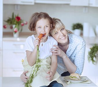 Mother and daughter with daughter eating carrot