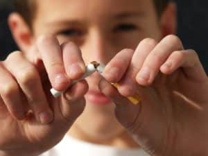 Quit smoking! a boy is breaking a cigarette in two.