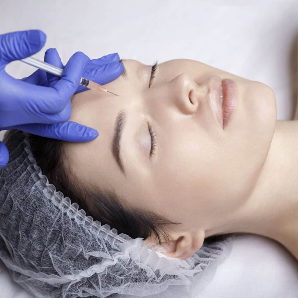 woman having needle to face Dermal Fillers