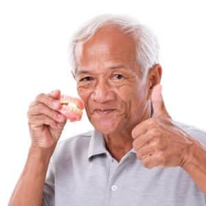 NHS dental patients fined - dentures senior man gives the thumbs up