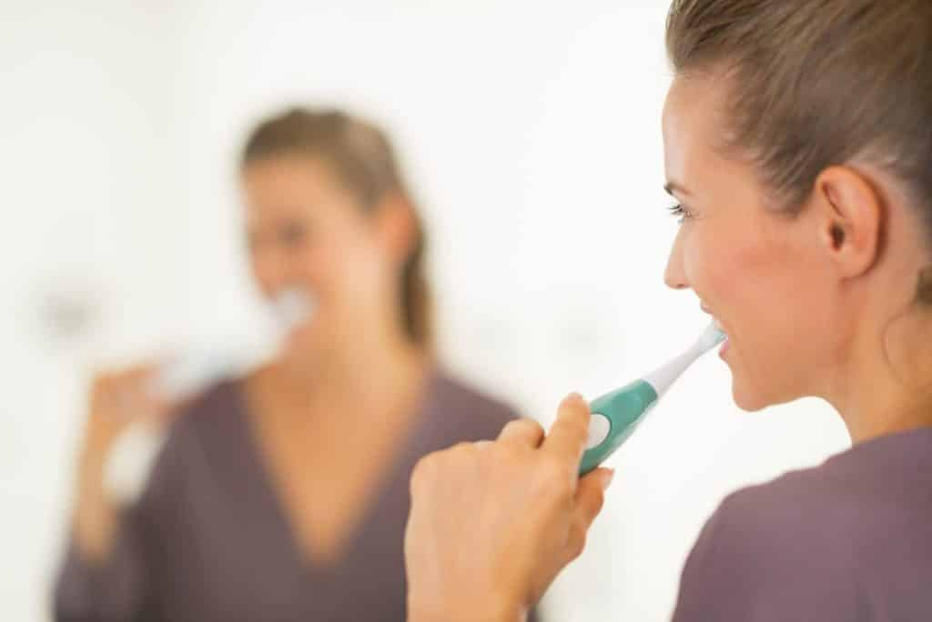 YOung woman brushing her teeth with an electric or manual toothbrush looks in the mirror.