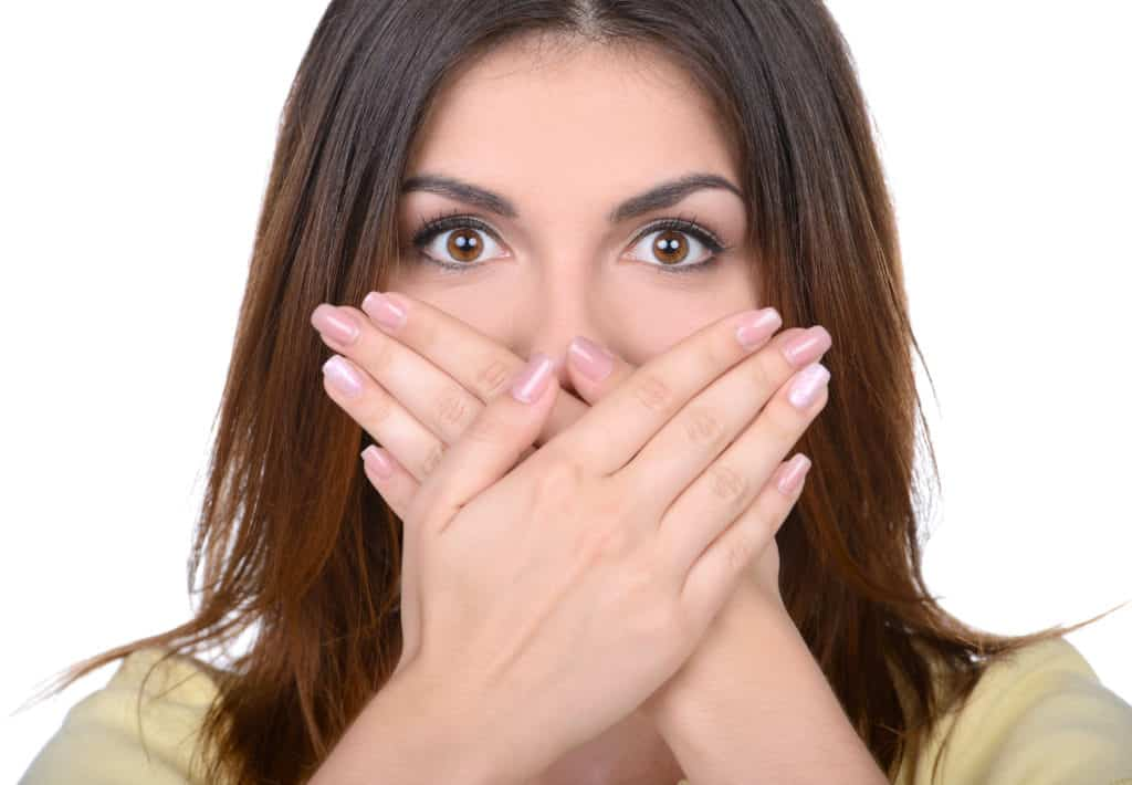 woman with hand over mouth for help sensitive teeth