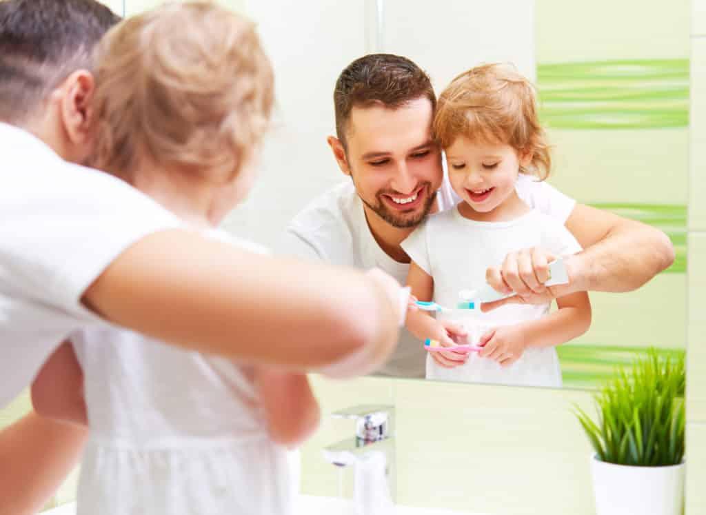 father brushing daughters teeth as a good anti sugar habit