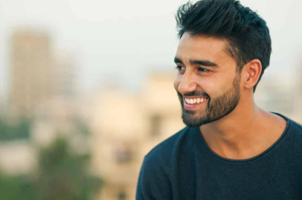 Young bearded man smiling. Dental health during Ramadan.