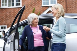 Female Neighbor Giving Senior Woman A Lift In Car to avoid NHS dental fines