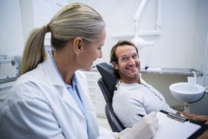 considering an implant shows a man talking to his dentist