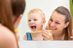 Dental care tips for babies and children as mother teaches infant to clean teeth