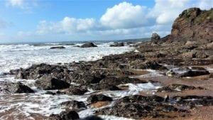 photo of sea and Devon coastline. Protect tooth enamel likes rocks against waves.
