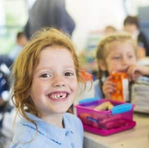 Girl with missing tooth and lunch box for school tooth care answers