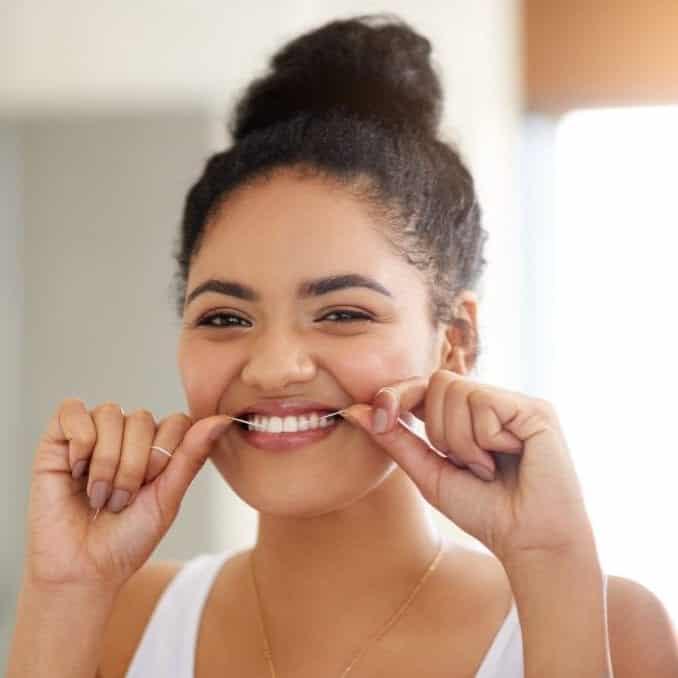 SpaDental Chard Essentials plan shows a woman flossing her teeth, Denplan Supplementary Insurance cover.