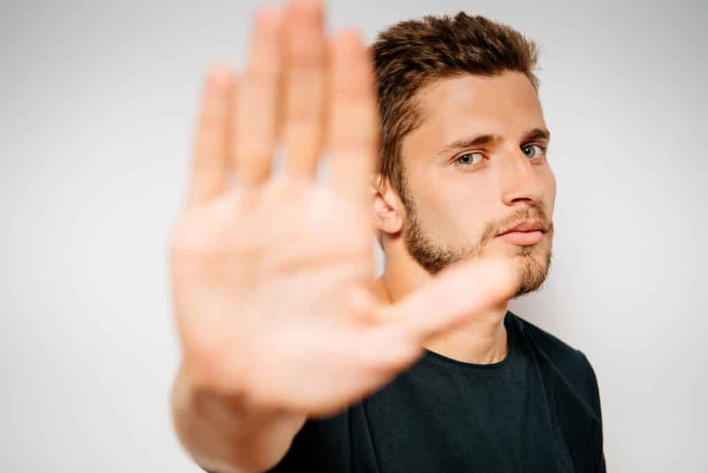 man raisees hand to stop smoking