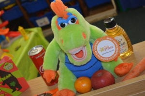 brush better helped by an orange and green toy dinosaur