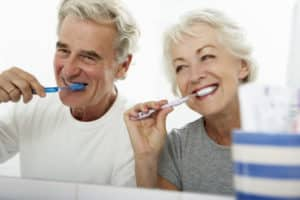 happy grey haired couple infront of mirror using manual toothbrushes