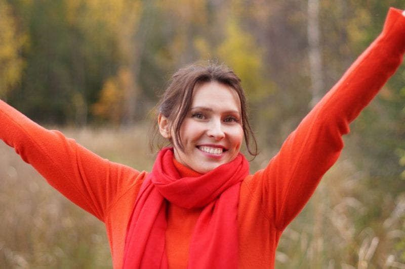 Woman with brown hair smiling, wears a red sweater for SpaDental Chard periodontal care
