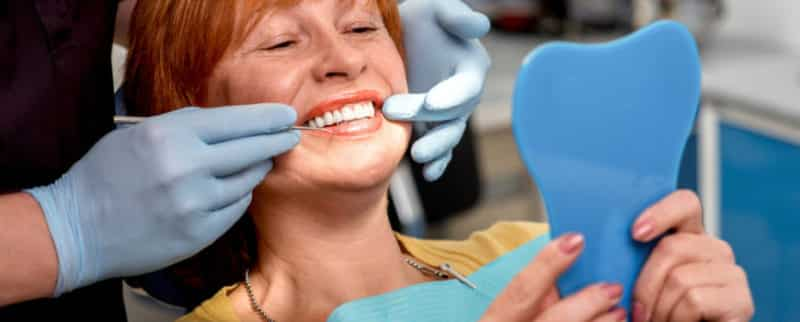 care for dental implants shows a woman having a dental check in surgery