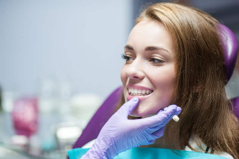 good dentist checking the colour and shape of a womans teeth. Wearing purple gloves.