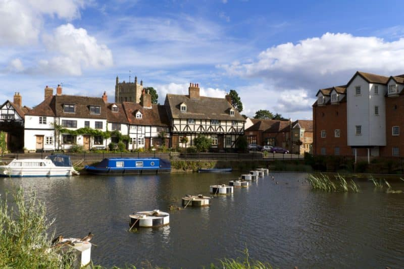 About Tewkesbury cottages by the river with cloudy but blue sky
