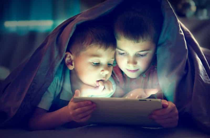 picture of two children abusing screen time after dark.