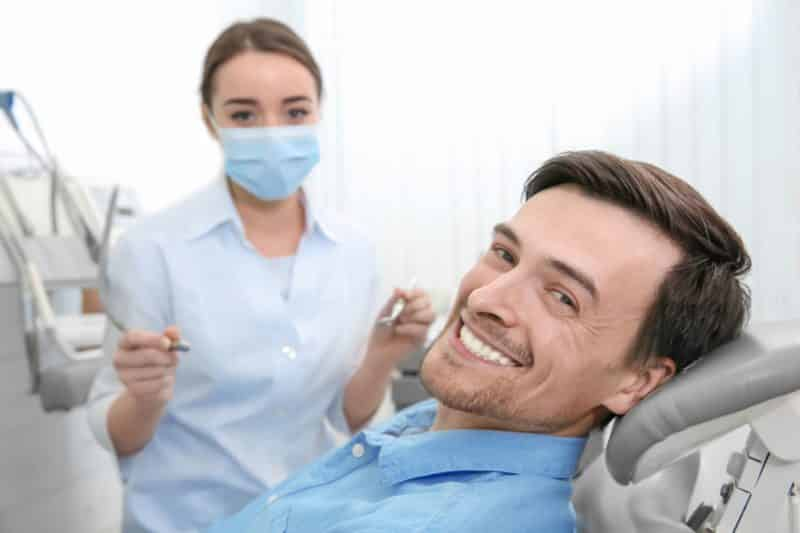 whitchurch dental therapist ready to work on a man's teeth. He's wearing a blue shirt and smiling.