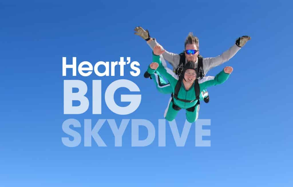 Two skydivers in a blue sky jumping for joy