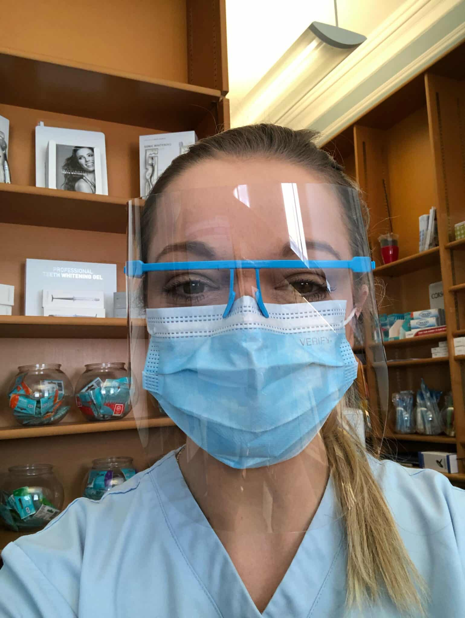 Nurse behind reception as dental staff in PPE meet patients