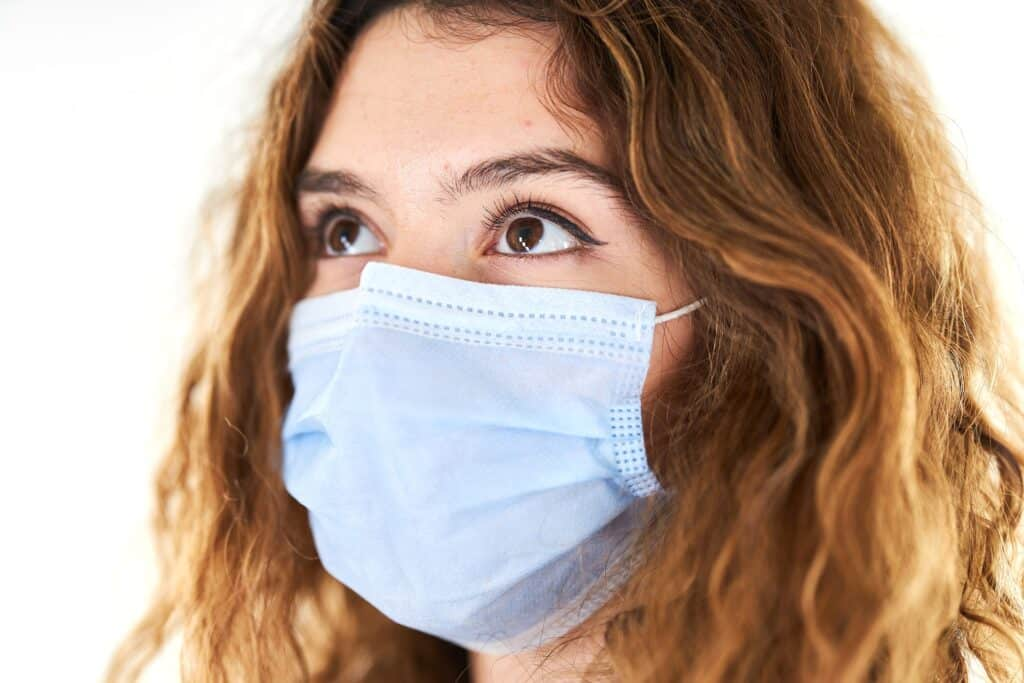 woman wearing surgical mask asks about dental costs post coronaviruspost-