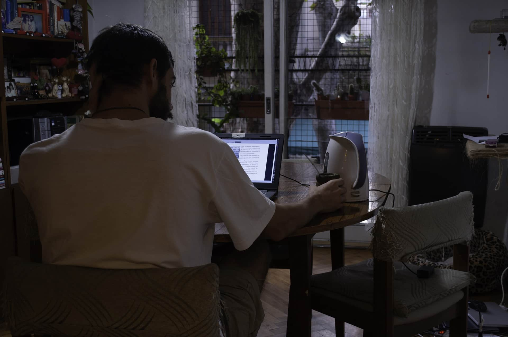 man working on laptop at home may have lockdown damage to back and teeth