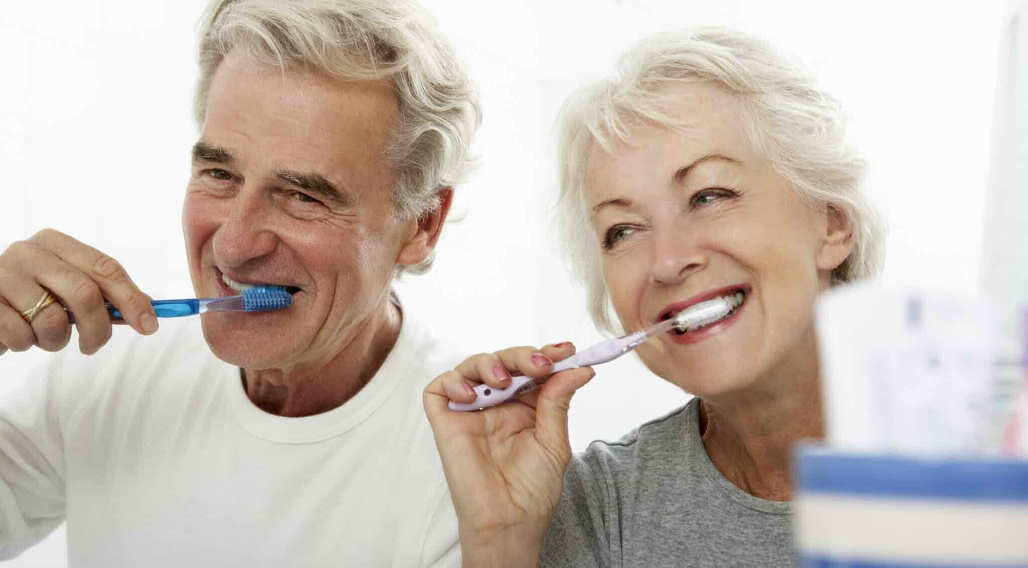 older couple brushing teeth in bathroom habits spread coronavirus