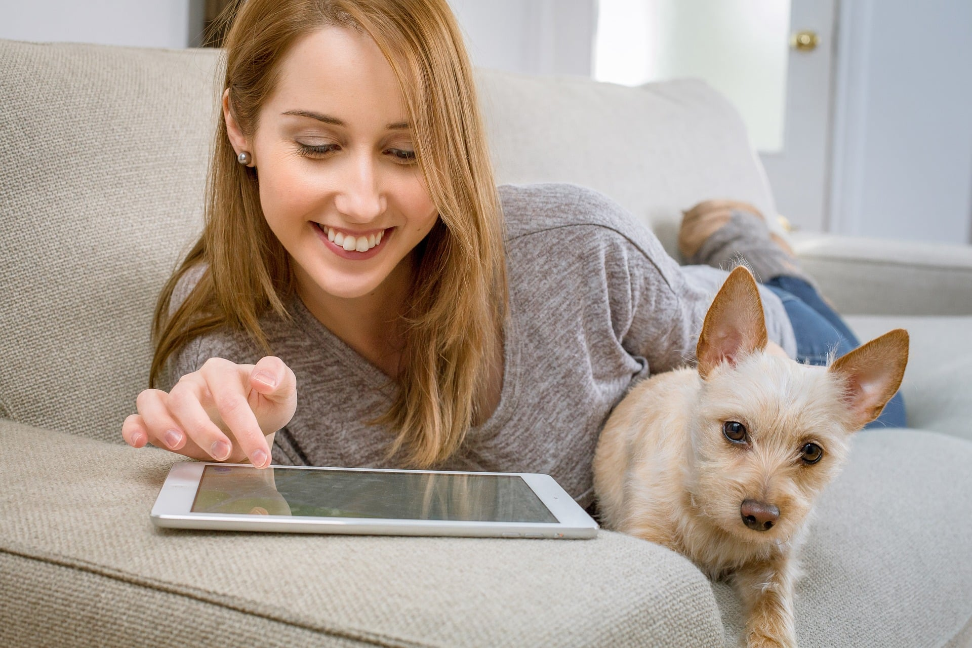 SpaDental top dental blogs with woman reading from a tablet and holding a dog
